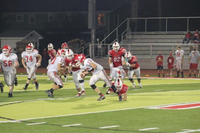 Port Clinton's Westin Laird tries to tackle Huron quarterback Cole Parker.