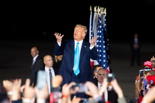 President Donald Trump reacts to the falling rain as he arrives to a campaign rally at Avflight Harrisburg at the Harrisburg International Airport on Saturday, September 26, 2020, in Middletown, Pa.