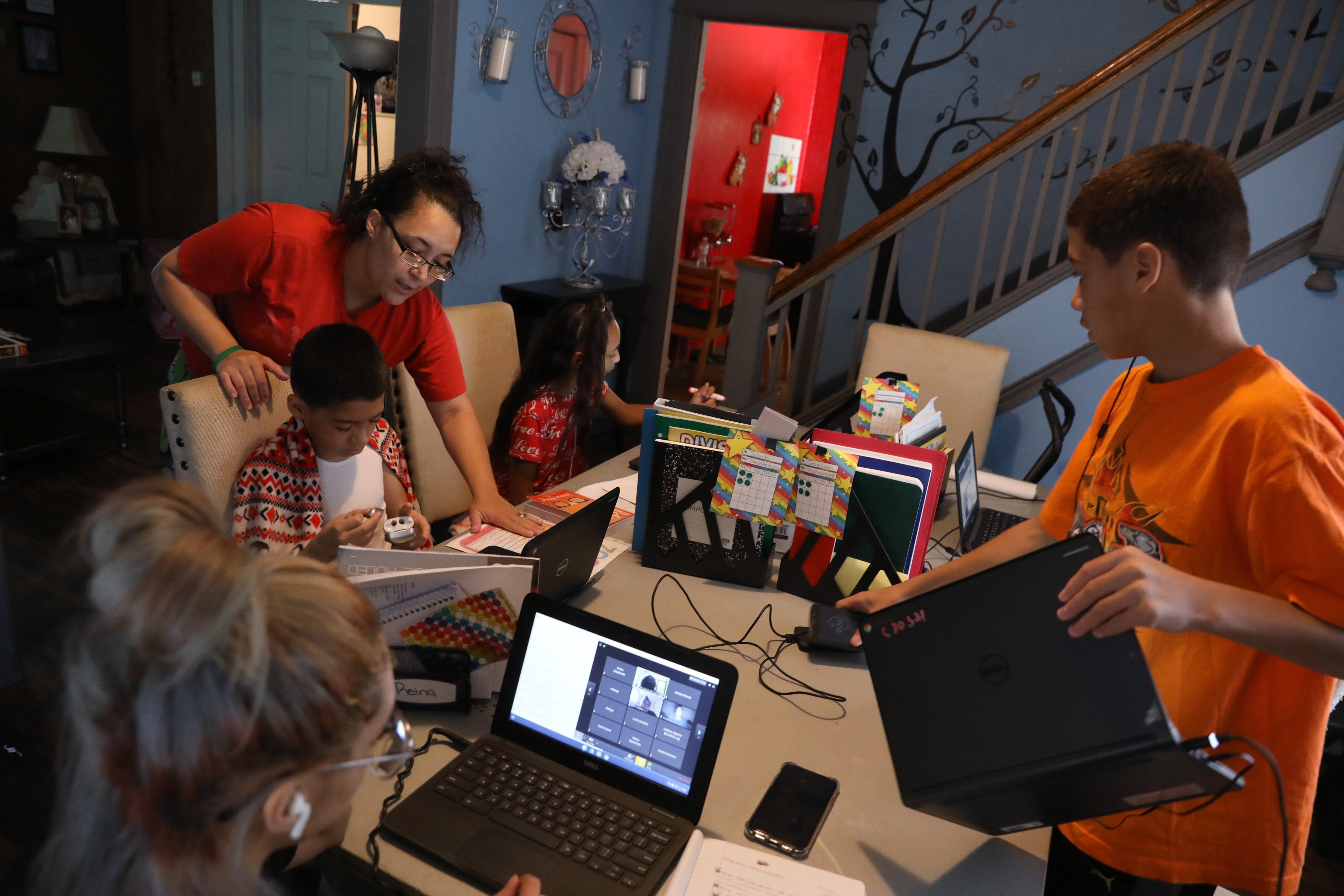 Mother Zumarie Sepulveda checks in on the progress of son Jacob, a fifth grader, and all her kids as they sit together in the living room for online learning from their schools at their home in Rochester Friday, Sept. 25, 2020.