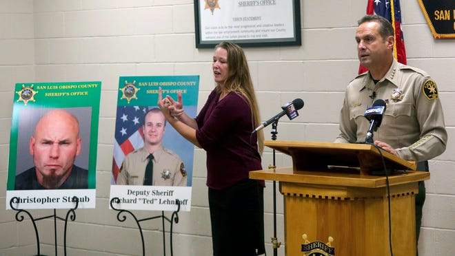 Sheriff Ian Parkinson, with interpreter Robin Babb, speaks during a press conference on Friday.