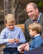 Prince George and Prince Louis with their father Prince William in the gardens of Kensington Palace, examining an ancient giant shark tooth given to George by David Attenborough.