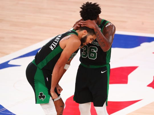 Boston Celtics guard Marcus Smart speaks with forward Jayson Tatum during the second half of Game 5 against the Miami Heat.