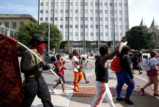 Protesters march in front of the headquarters of the Akron Police Department during a march of the Ohio Community Coalition Akron Chapter protesting the March killing of Breonna Taylor by members of the Louisville, Kentucky, police department Sunday in Akron. [Karen Schiely/Beacon Journal]