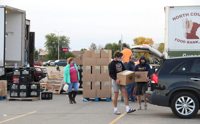 Volunteers, including Crookston High School student-athletes, place protein and dairy products into vehicles at CHS on Saturday.