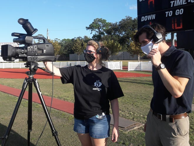 Bishop Kenny High School sophomore Parker Harms (left) sets up a camera, with supervision from teacher and CrusaderVision program co-sponsor Morgan Hale, behind an end zone before a high school football game against West Nassau on Sept. 25. The COVID-19 pandemic has increased interest in remote broadcasts for those unable to attend high school events in person.