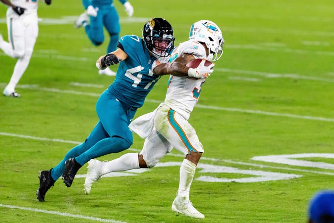 Dolphins running back Myles Gaskin (37) attempts to break away from Jaguars linebacker Joe Schobert (47) during Thursday night's game. Matt Pendleton/Special to the Times-Union