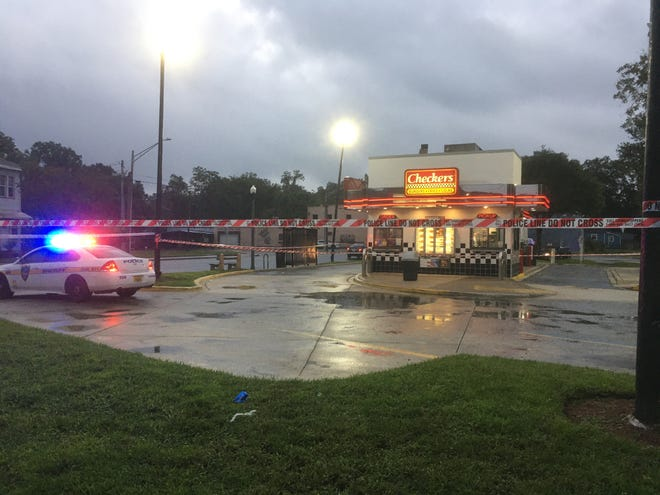 Police seal off the Checkers at Kings Road and Rushing Street while investigators look for evidence from a fatal shooting in the parking lot Sunday.