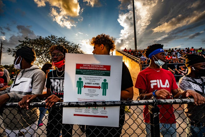 Lakeland High football fans watch the action against Lake Gibson from behind a social distancing poster at Bryant Stadium on Friday night.