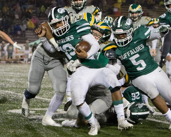 Khalid Robinson (19) from Manteca carries the defensive line with him to get the first down late in the fourth quarter against Placer in the Sac-Joaquin Section Championship game at Hughes Stadium on Nov. 30th.