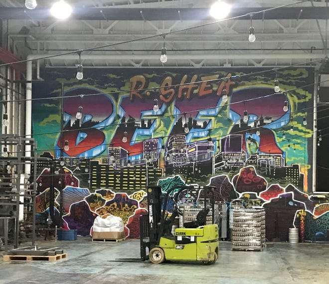 The brewing facility at R. Shea Brewery boasts a massive mural with the company's name and a skyline.