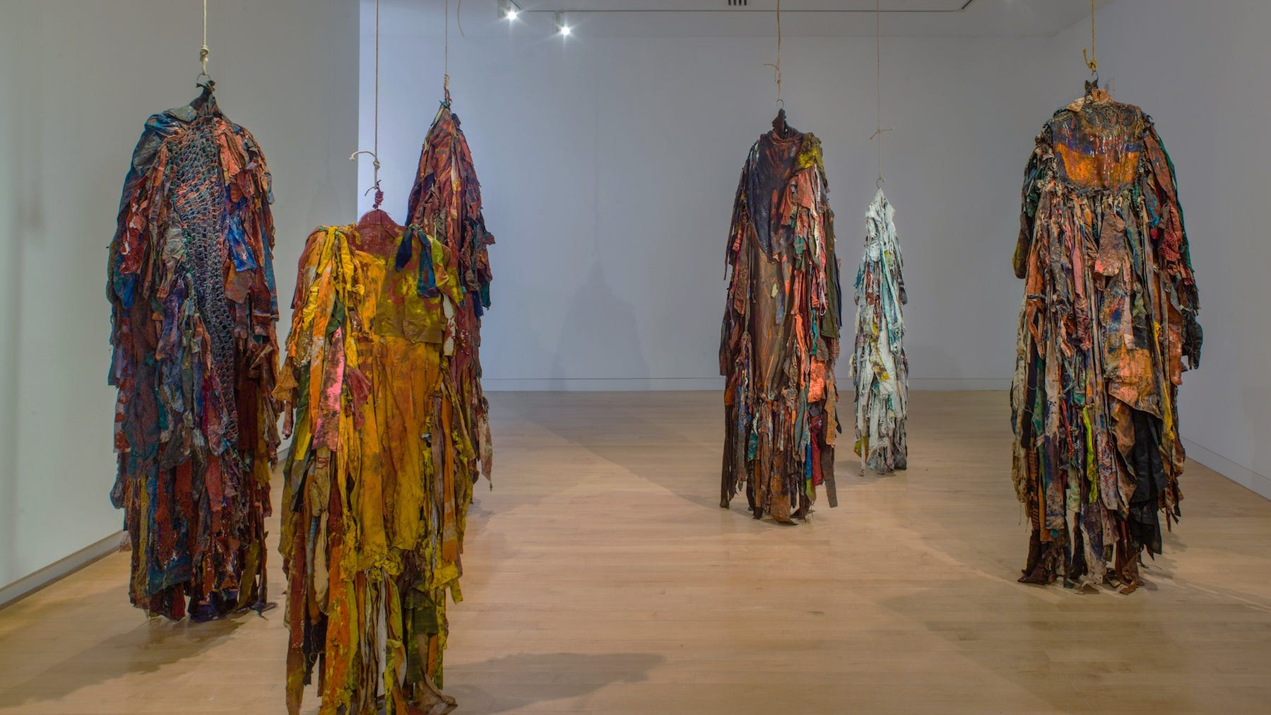 """""""Presences"""" recreates a 1973 installation by Harmony Hammond featuring strips of recycled cloth, suspended by coat hangers."""