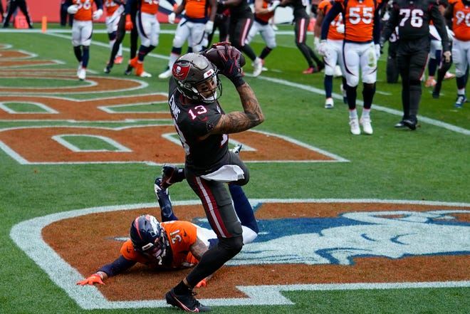 Tampa Bay Buccaneers WR Mike Evans makes a catch in the end zone for a touchdown as Denver Broncos free safety Justin Simmons defends during the first half Sunday in Denver. The Bucs won 28-10.