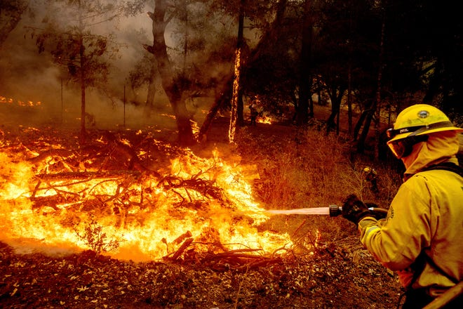 A firefighter battles the Glass Fire burning in Calistoga, Calif., on Sunday, Sept. 27, 2020.
