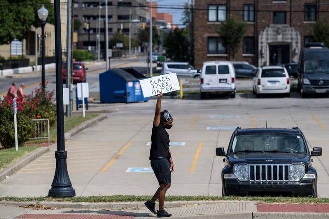 Wusef Dixon hoists up a sign during a Black Lives Matter protest along Riverside Drive in Downtown Evansville, Ind., Sunday afternoon, Sept. 27, 2020.