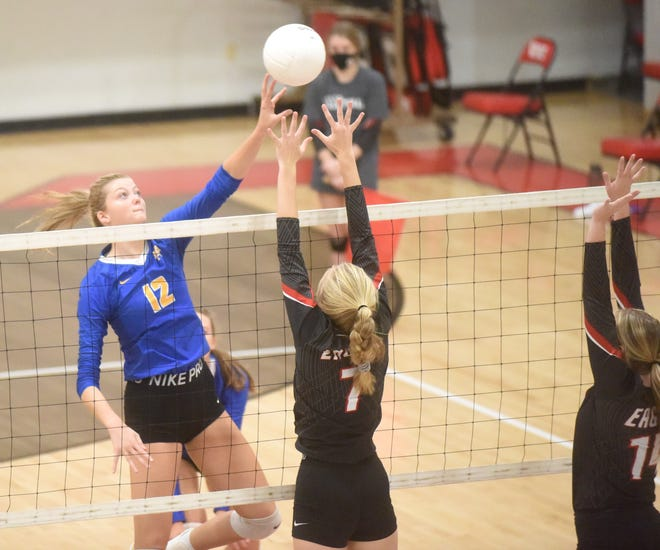 Mountain Home's Reanna Dodge tips over Vilonia's Madison Wright during the Lady Bombers' three-set sweep Saturday at Vilonia.