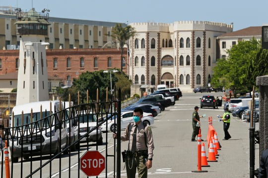 """In this July 9, 2020, file photo, a correctional officer closes the main gate at San Quentin State Prison in San Quentin, Calif. On Saturday, Sept. 26, 2020, Gov. Gavin Newsom signed a law that requires the state to house transgender prisoners based on their gender identity. The law does have an exception for """"management or security concerns."""""""