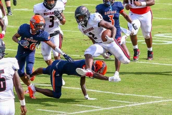 West Florida Tech's Simeon Price (2) leaps to avoid a Gators defender on Saturday, Sept. 26, 2020, during the season-opening game at Escambia High School. The Gators won 24-20.