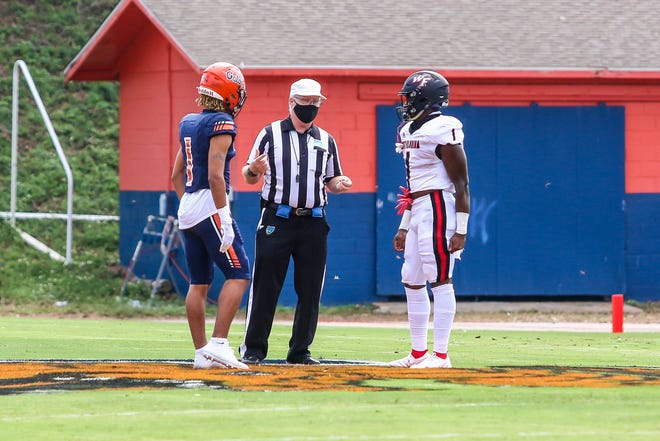 Escambia's Jojo Blackmon, left, and West Florida Tech's Jaheim Simmons, right, prepare for the opening coin toss before their game on Saturday, Sept. 26, 2020. Normally there are multiple captains from each team at midfield for the coin toss. However, due to COVID-19 precautions this year, only one captain from each team participates.