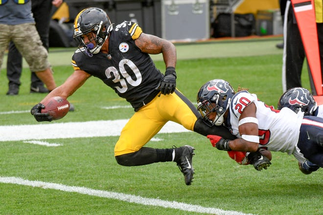 Pittsburgh Steelers running back James Conner (30) stretches for the end zone to score as Houston Texans strong safety Justin Reid (20) tries to bring him down in the second half of an NFL football game, Sunday, Sept. 27, 2020, in Pittsburgh. (AP Photo/Don Wright)