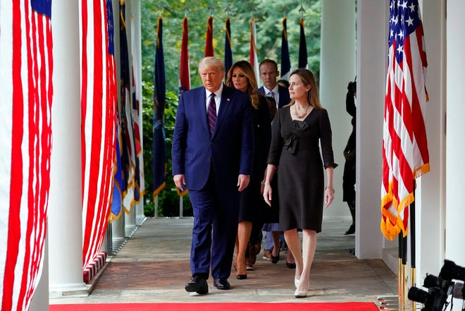 President Donald Trump walks along the Colonnadewith Judge Amy Coney Barrett to a news conference to announce Barrett as his nominee to the Supreme Court, in the Rose Garden at the White House, Saturday, Sept. 26, 2020, in Washington. (AP Photo/Alex Brandon)