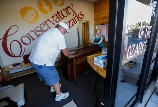 Brian Dealy and Heather Leverich, founder of the Conservatory of the Ozarks, move a piano out to Dealy's truck on Saturday, Sept. 26, 2020. The conservatory has had to close its doors due to the impact of COVID-19.