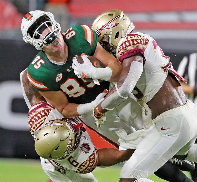UM's tight end Will Mallory (85) gets squeezed by FSU's Jaiden Lars-Woodbey (6) and Amari Gainer (33) in the first quarter as the University of Miami host Florida State University Seminoles at Hard Rock Stadium in Miami Gardens on Saturday, September 26, 2020.