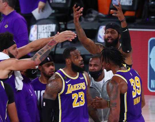 Los Angeles Lakers forward LeBron James celebrates with teammates during the fourth quarter of Game 5 against the Denver Nuggets.