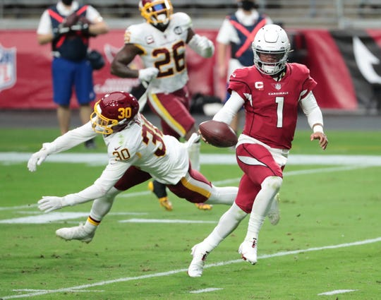 Arizona Cardinals quarterback Kyler Murray (1) avoids Washington Football Team free safety Troy Apke (30) during a touchdown run during the fourth quarter at State Farm Stadium Sept. 20, 2020.
