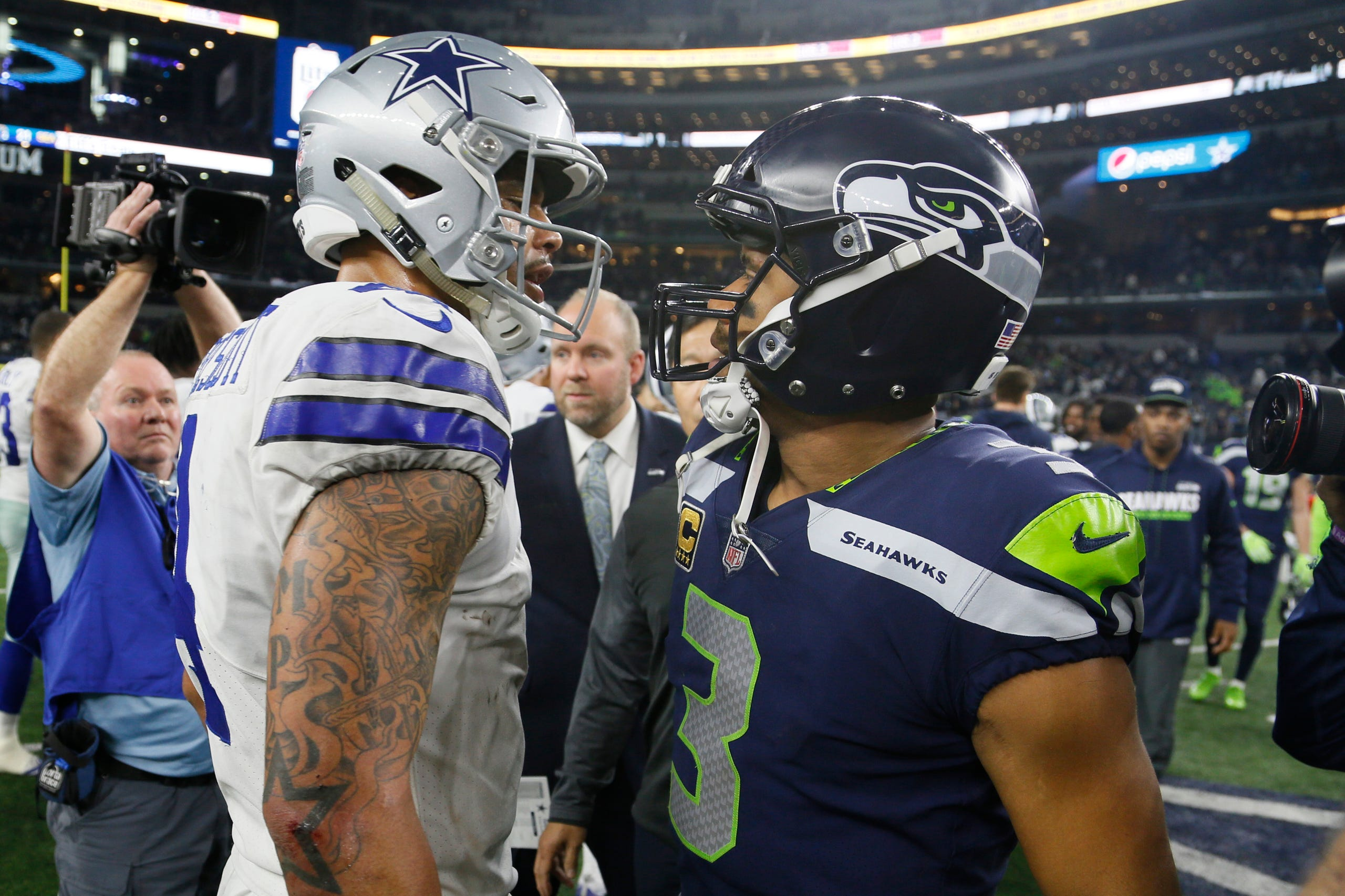 Dallas Cowboys quarterback Dak Prescott (4) meets with Seattle Seahawks quarterback Russell Wilson (3) after a game at AT&T Stadium.