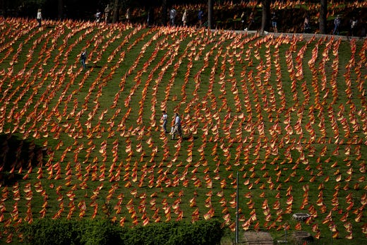 People walk among the Spanish flags placed in memory of coronavirus (COVID-19) victims in Madrid, Spain, Sunday, Sept. 27, 2020. An association of families of coronavirus victims has planted what it says are 53,000 small Spanish flags in a Madrid park to honor the dead of the pandemic.