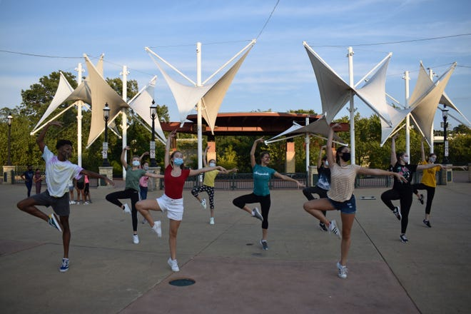 Jonathan McCray Jr., from left, Clara Woods, Kyla Hayashi, Vivian Gray, Adalyn Zorich, Megan Murphy, Lex Zorich, Maggie Stone, Hannah Kennell and Madison Teets from Ballet Excel Ohio do a pop-up performance on Front Street in Cuyahoga Falls Saturday.