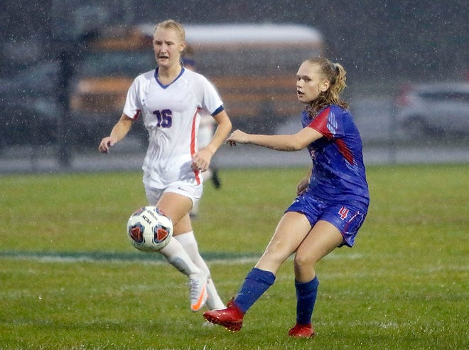 Mapleton's Hailey Devore (4) sends the ball down the field against Edison's Autumn Canterbury (16) during high school girls soccer action Monday at Mapleton High School. The Mounties won, 2-1.