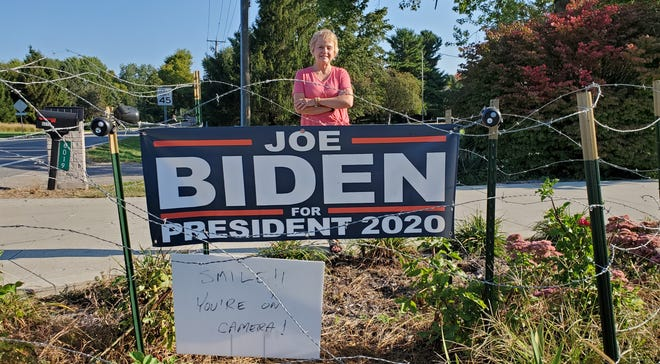 Befitting a battleground state, Char Anderson and her husband, Steve, turned to barbed wire and security cameras to protect the large Biden sign outside their Genoa Township home after two earlier signs were stolen. [Randy Ludlow/Dispatch]