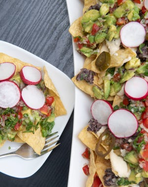 Vegetarian nachos are a meal in itself. It is loaded with corn tortilla chips, pico de gallo, guacamole, queso and black beans, and garnished with radish and pickled jalapenos.