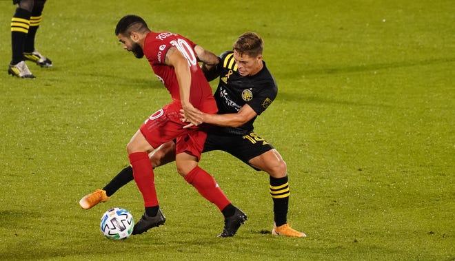 Toronto FC midfielder Alejandro Pozuelo (10) works the ball against Columbus Crew midfielder Sebastian Berhalter (18) in the first half on Sunday night at Pratt & Whitney Stadium in Hartford, Conn.