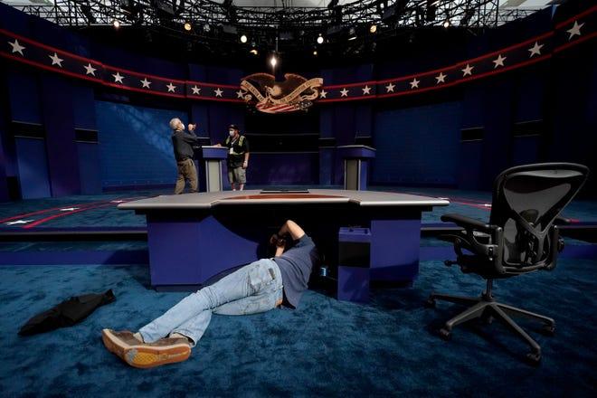 A technician works under the desk where moderator Chris Wallace of Fox News will set Tuesday night during the debate between President Donald Trump and Democrat Joe Biden. [Julio Cortez/The Associated Press]