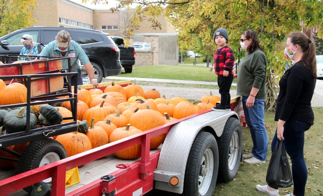 """At Saturday's Cornstalk Jamboree and farmers' market at Town Square, Connor Neuman was interested in Bob Prudhomme's trailer full of pumpkins, until he spotted a photographer nearby and looked at the camera, smiled, and said, """"Cheeeeeeeeeese!"""" Connor's mom, Laura Neuman, is standing on the far right."""