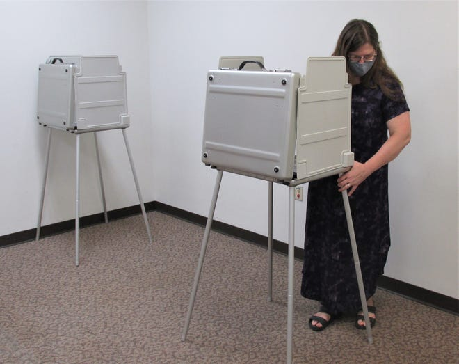 Holmes County Board of Elections Director Lisa Welch sets up a portable voting  booth in the new office space in the Clinton Street office of the Holmes BOE.