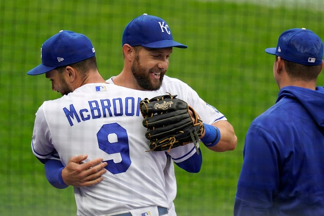 Kansas City Royals left fielder Alex Gordon, middle, is hugged by teammate Ryan McBroom (9) after being taken out of a baseball game against the Detroit Tigers during the second inning at Kauffman Stadium. It was Gordon's last game as a Royal.