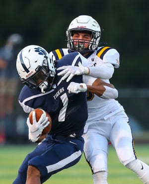 Twinsburg senior Alex Branch attempts to shuck off a Tallmadge defender during the Tigers' 24-20 home loss to the Blue Devils Sept. 25.