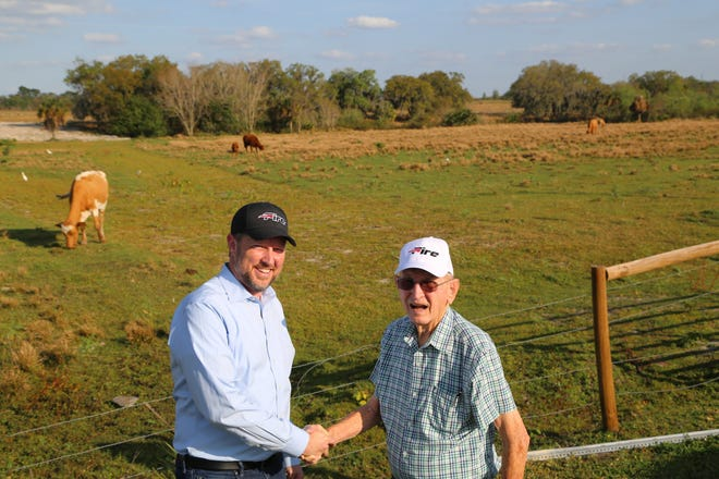 Southeastern University Athletic Director Drew Watson, left, stands with Ed Holloway at the 36 acres of land Holloway and his wife Mary Ann donated to the university.
