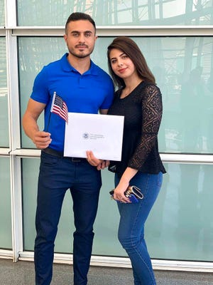 """In this September 2019 photo provided by Jad """"Jay"""" Jawad, Jawad, left, who came to the U.S. as a refugee from war-torn Iraq, poses at his naturalization ceremony in Phoenix with his wife, Nagham Rabeea, right. Jawad's parents and siblings are also settled in Arizona. He said that during presidential elections in his native country, Saddam Hussein was the only candidate on the ballot and the only real option was """"yes,"""" because a """"no"""" vote could get you jailed or worse. Now, he said he is looking to voting freely in his first U.S. presidential election this fall."""