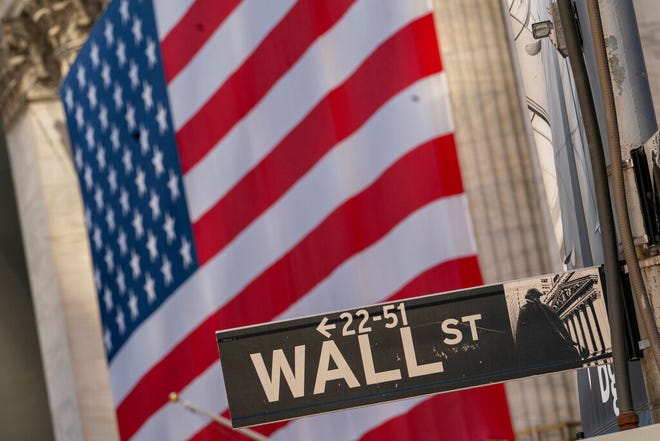 The Wall Street street sign is framed by a giant American flag hanging on the New York Stock Exchange, in a Monday, Sept. 21, 2020 file photo. Stocks are opening higher on Wall Street, recovering after their first four-week losing streak in more than a year. A burst of corporate deals helped give investors confidence to put money back in the market, and the S&P 500 rose 1.4% in the early going Monday, Sept. 28, 2020.