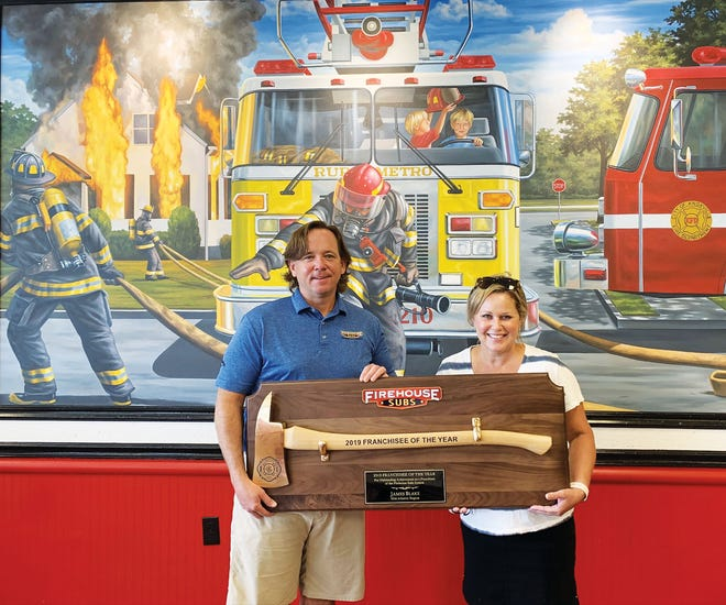 Husband and wife franchisee duo James and Susan Blake show the Axe Award in front of a mural in Firehouse Subs. They own eight Firehouse Subs in the area, including the one in Oak Ridge at Manhattan Place.