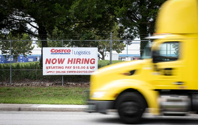 A semi-truck and trailer makes its way along Southwest 46th Avenue in Ocala by a banner advertising Costco Wholesale logistics jobs. The sign caused excitement after some residents thought that it meant a Costco store was coming to the area.