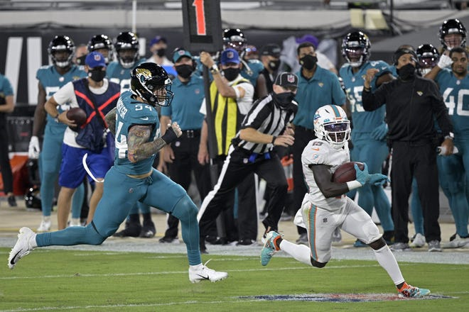 Dolphins receiver Jakeem Grant runs 29 yards on an end-around as Jacksonville's Cassius Marsh tries to defend.