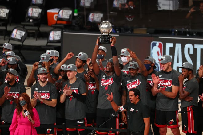 Heat forward Bam Adebayo, who scored a season-high 32 points and grabbed 14 rebounds Sunday, holds up the Eastern Conference Championship trophy amid his celebrating teammates after Miami eliminated the Boston Celtics in Game Six in Lake Buena Vista.