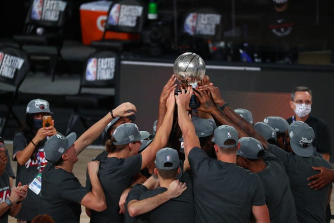Heat players hold up the Eastern Conference Championship trophy after defeating the Celtics on Sunday night in Lake Buena Vista.