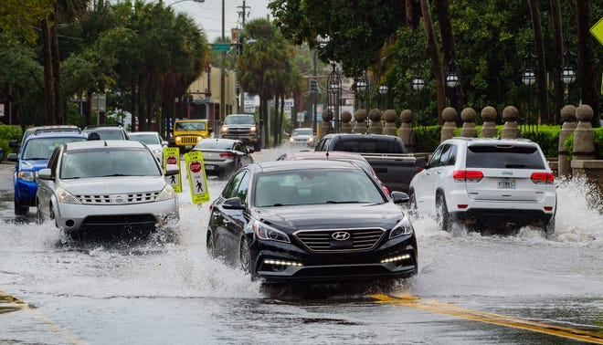 Vehicles travel down a flooded King Street in St. Augustine after a rain storm on Monday, September 28, 2020.
