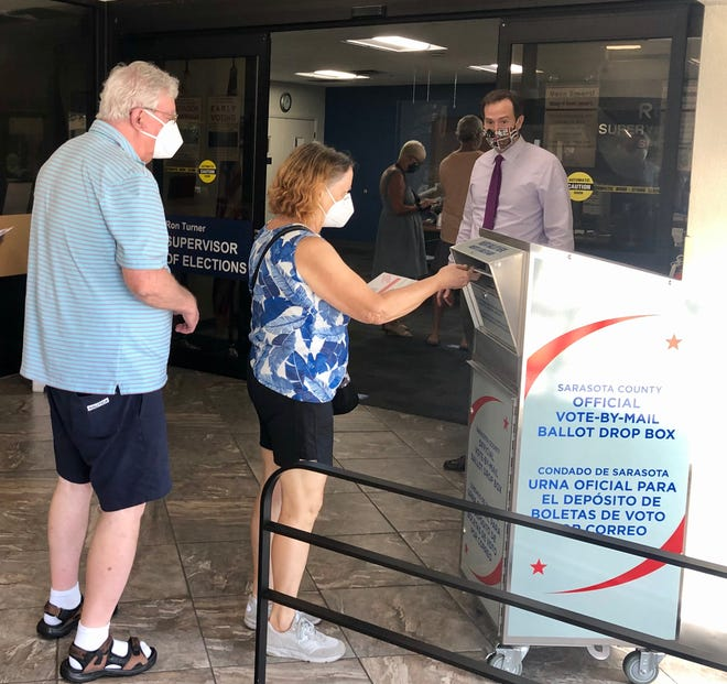 Sarasota residents Tom and Patricia Flynn dropped off their mail ballots at the Sarasota County Supervisor of Elections downtown office Monday.